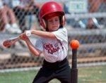 Young boy hitting baseball off of a tee.